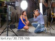 Купить «Professional photo shooting outdoors. Attractive female model posing to photographer on city street», фото № 30739166, снято 5 октября 2018 г. (c) Яков Филимонов / Фотобанк Лори