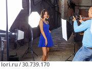 Купить «Professional photo shooting outdoors. Attractive female model posing to photographer on city street», фото № 30739170, снято 5 октября 2018 г. (c) Яков Филимонов / Фотобанк Лори