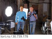 Купить «two photographers standing with cameras among professional photo equipment», фото № 30739178, снято 5 октября 2018 г. (c) Яков Филимонов / Фотобанк Лори