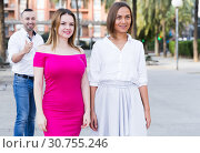 Купить «Young women are walking and stranger man is want acquaintance with them», фото № 30755246, снято 18 октября 2017 г. (c) Яков Филимонов / Фотобанк Лори