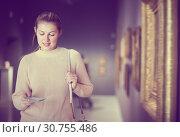 Купить «Joyful girl holding guide book in museum», фото № 30755486, снято 18 ноября 2017 г. (c) Яков Филимонов / Фотобанк Лори
