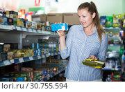 Купить «Young woman in the shop holding preserved of tuna», фото № 30755594, снято 5 августа 2017 г. (c) Яков Филимонов / Фотобанк Лори