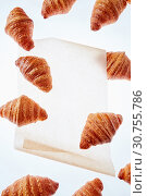Floating freshly baked croissant on a light background of parchment paper, mock up. Стоковое фото, фотограф Ярослав Данильченко / Фотобанк Лори