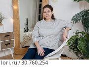 Купить «Calm attractive woman sitting in rattan chair in domestic room behind mirror, looking at camera», фото № 30760254, снято 17 февраля 2019 г. (c) Кекяляйнен Андрей / Фотобанк Лори