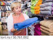 mature woman holding cotton colour towel in the textile shop. Стоковое фото, фотограф Яков Филимонов / Фотобанк Лори