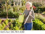 Купить «Woman posing with watering can in garden», фото № 30761030, снято 3 октября 2018 г. (c) Яков Филимонов / Фотобанк Лори