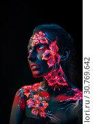 Купить «Beautiful flowers in UV light on a young girl face and body», фото № 30769642, снято 5 апреля 2019 г. (c) Sergii Zarev / Фотобанк Лори
