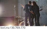 Купить «A repetition. A young group of people playing rock music and discussing it», видеоролик № 30769770, снято 6 июля 2020 г. (c) Константин Шишкин / Фотобанк Лори