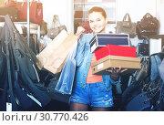 Купить «portrait of teenage girl standing with bags in store with bags», фото № 30770426, снято 15 сентября 2016 г. (c) Яков Филимонов / Фотобанк Лори