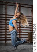 Купить «Woman practicing pole dancing in dark studio», фото № 30770606, снято 10 мая 2018 г. (c) Яков Филимонов / Фотобанк Лори