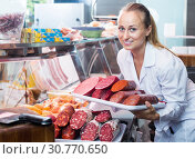 Купить «Seller woman picking tray with various salami», фото № 30770650, снято 20 июля 2019 г. (c) Яков Филимонов / Фотобанк Лори