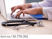 Young male doctor in telemedicine concept. Стоковое фото, фотограф Elnur / Фотобанк Лори