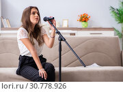 Купить «Female beautiful musician singing at home», фото № 30778926, снято 1 октября 2018 г. (c) Elnur / Фотобанк Лори