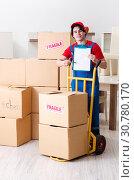 Купить «Young male contractor with boxes working indoors», фото № 30780170, снято 1 февраля 2019 г. (c) Elnur / Фотобанк Лори