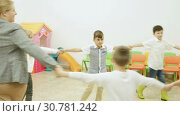 Купить «Group of happy children dancing in circle holding hands with their teacher in classroom during recess», видеоролик № 30781242, снято 18 декабря 2018 г. (c) Яков Филимонов / Фотобанк Лори