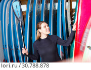 Happy girl in wetsuit holding paddle, standing near rack with boards for paddleboarding. Стоковое фото, фотограф Яков Филимонов / Фотобанк Лори