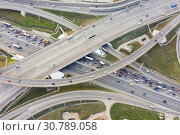 Купить «Aerial view of road junction in Moscow from above, automobile traffic and jam of many cars, road junction on the Moscow Ring Road and the M11 toll road», фото № 30789058, снято 8 декабря 2019 г. (c) Mikhail Starodubov / Фотобанк Лори