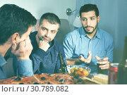 Купить «Troubled male friends talking, drinking beer with pizza at home», фото № 30789082, снято 10 января 2018 г. (c) Яков Филимонов / Фотобанк Лори
