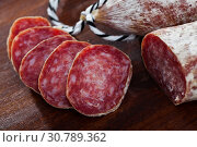 Купить «Spanish longaniza salami sausages cut in slices on a woodefn desk», фото № 30789362, снято 18 июля 2019 г. (c) Яков Филимонов / Фотобанк Лори