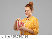 Купить «smiling red haired teenage girl eating popcorn», фото № 30790186, снято 28 февраля 2019 г. (c) Syda Productions / Фотобанк Лори