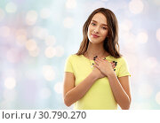 Купить «smiling teenage girl holding hands on heart», фото № 30790270, снято 29 января 2019 г. (c) Syda Productions / Фотобанк Лори