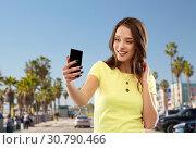 Купить «teen girl takes selfie by cell over venice beach», фото № 30790466, снято 29 января 2019 г. (c) Syda Productions / Фотобанк Лори