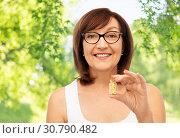 Купить «senior woman with gold facial mask in bottle», фото № 30790482, снято 8 февраля 2019 г. (c) Syda Productions / Фотобанк Лори