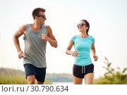 Купить «couple in sports clothes running along on beach», фото № 30790634, снято 1 августа 2018 г. (c) Syda Productions / Фотобанк Лори