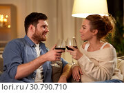 Купить «happy couple drinking red wine at home in evening», фото № 30790710, снято 5 января 2019 г. (c) Syda Productions / Фотобанк Лори