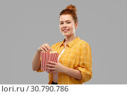 Купить «smiling red haired teenage girl eating popcorn», фото № 30790786, снято 28 февраля 2019 г. (c) Syda Productions / Фотобанк Лори