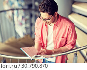 Купить «student boy or young man reading book at library», фото № 30790870, снято 19 июня 2016 г. (c) Syda Productions / Фотобанк Лори