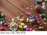 Купить «chocolate eggs and candy drops on wooden table», фото № 30790978, снято 22 марта 2018 г. (c) Syda Productions / Фотобанк Лори