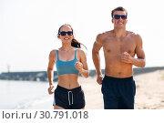 Купить «couple in sports clothes running along on beach», фото № 30791018, снято 1 августа 2018 г. (c) Syda Productions / Фотобанк Лори