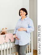 happy pregnant woman next to baby bed at home. Стоковое фото, фотограф Syda Productions / Фотобанк Лори