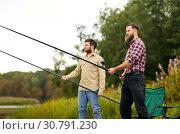 Купить «friends with fishing rods at lake or river», фото № 30791230, снято 8 сентября 2018 г. (c) Syda Productions / Фотобанк Лори