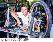 Купить «Man repairing bicycles with instruments indoors», фото № 30791286, снято 17 июля 2017 г. (c) Яков Филимонов / Фотобанк Лори