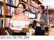 Купить «girl browsing textbooks in bookstore», фото № 30791294, снято 18 января 2018 г. (c) Яков Филимонов / Фотобанк Лори