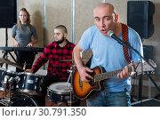Купить «Nice male singer rehearsing with band», фото № 30791350, снято 26 октября 2018 г. (c) Яков Филимонов / Фотобанк Лори