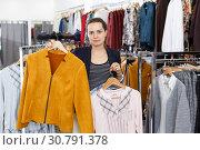 Купить «Woman holding lot of hanger with clothes», фото № 30791378, снято 10 октября 2018 г. (c) Яков Филимонов / Фотобанк Лори