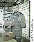Купить «Man seller going through boxes with door», фото № 30791562, снято 5 апреля 2017 г. (c) Яков Филимонов / Фотобанк Лори