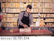 Купить «Smiling male seller sorting boxes with door details», фото № 30791574, снято 5 апреля 2017 г. (c) Яков Филимонов / Фотобанк Лори