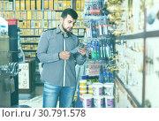 Купить «Man client choosing new hot glue in shop», фото № 30791578, снято 5 апреля 2017 г. (c) Яков Филимонов / Фотобанк Лори