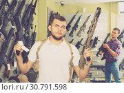 Купить «Male is choosing pneumatic gun», фото № 30791598, снято 4 июля 2017 г. (c) Яков Филимонов / Фотобанк Лори
