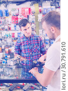 Купить «Male shopping assistant helping to buy pneumatic weapon in military shop», фото № 30791610, снято 4 июля 2017 г. (c) Яков Филимонов / Фотобанк Лори