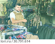 Купить «man with flak jacket in hands in airsoft market», фото № 30791614, снято 4 июля 2017 г. (c) Яков Филимонов / Фотобанк Лори