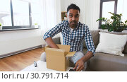 Купить «male blogger taking smartphone out of parcel box», видеоролик № 30791714, снято 26 апреля 2019 г. (c) Syda Productions / Фотобанк Лори