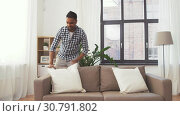Купить «indian man arranging sofa cushions at home», видеоролик № 30791802, снято 27 апреля 2019 г. (c) Syda Productions / Фотобанк Лори