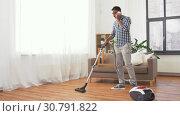 Купить «man with vacuum cleaner calling on cell at home», видеоролик № 30791822, снято 27 апреля 2019 г. (c) Syda Productions / Фотобанк Лори
