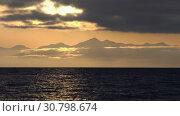 Вечерний морской пейзаж, облака, подсвеченные солнцем на закате, с видом на горы на горизонте. Стоковое видео, видеограф А. А. Пирагис / Фотобанк Лори