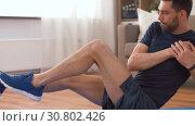 Купить «man making abdominal exercises at home», видеоролик № 30802426, снято 15 мая 2019 г. (c) Syda Productions / Фотобанк Лори
